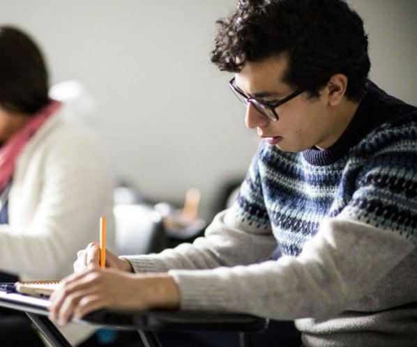 Estudiante sentado en un pupitre responde un ejercicio