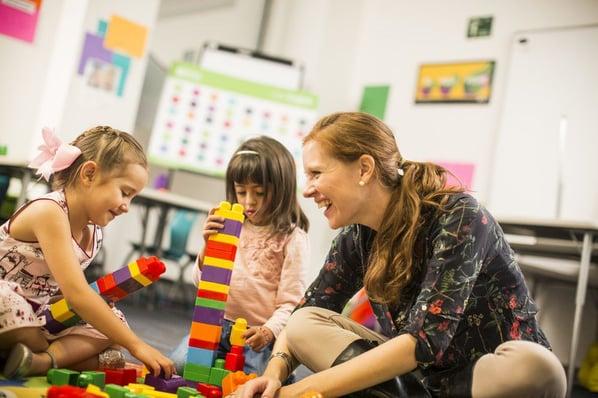 Maestra y niñas juegan con legos