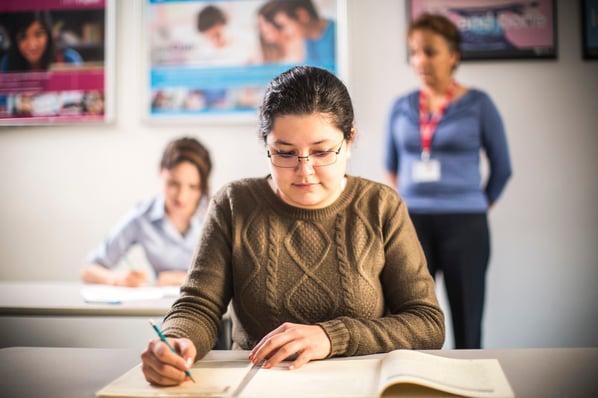 Mujer resuelve un examen IELTS, detrás de ella una profesora la vigila.