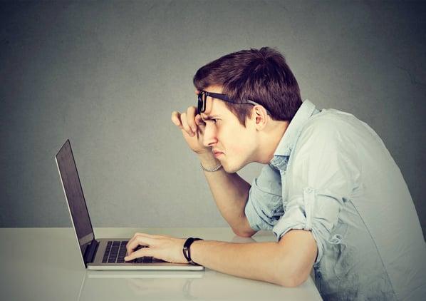 Joven se quita los lentes para ver de cerca una laptop-1