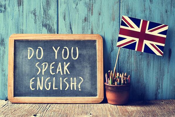 Pizarrón con frase escrita Do you speak english y junto a él una bandera de Reino Unido junto a unas crayolas