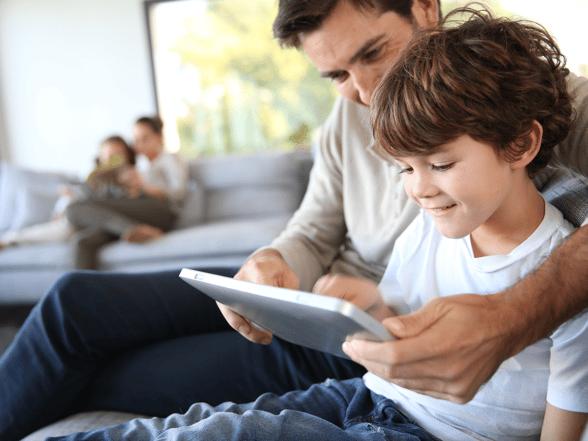 Un niño jugando desde su casa con su padre en una tablet