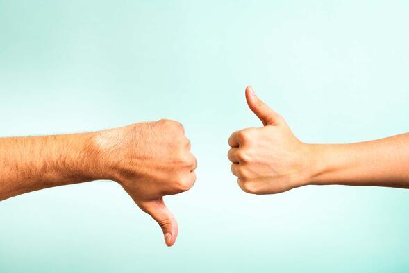 Una mano de hombre y una de mujer con los pulgares en aprobación y desaprobación respectivamente